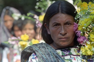 An indigenous woman carries flowers during a ceremony marking the sixth anniversary of the Atitlan massacre,